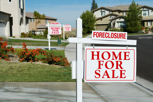 Foreclosure Home for Sale Signs in a Street
