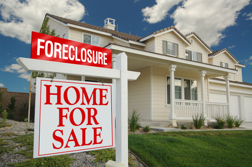 Foreclosure Home for Sale Sign in front of a Big House