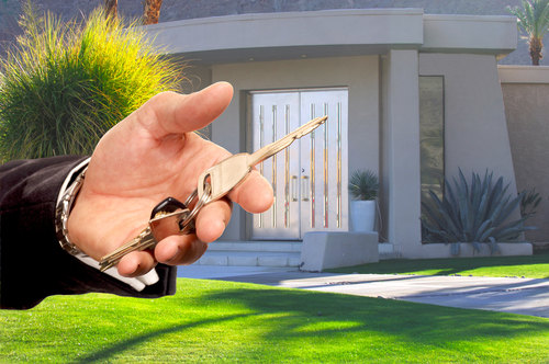 Hand with a Key and a House in the Background