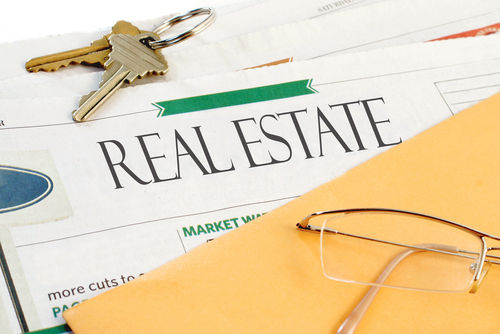 Real Estate Section of the Newspaper with Yellow Envelope Eyeglasses and Keys